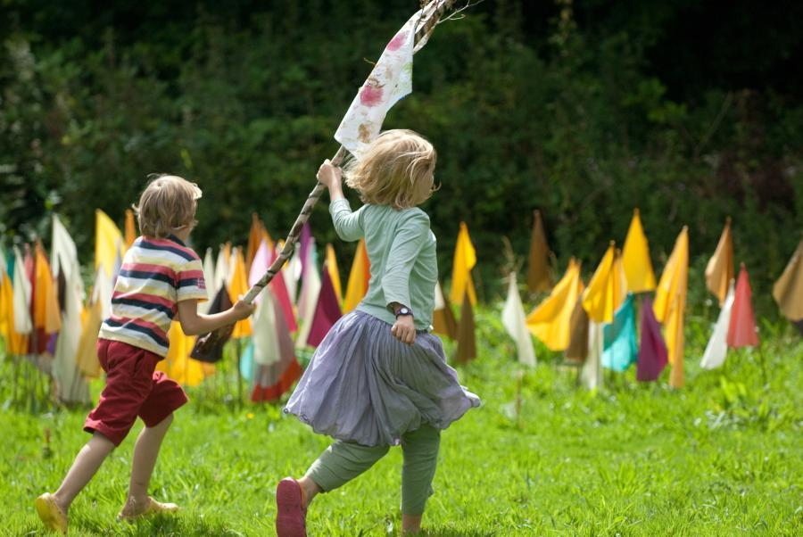 Two children capture a flag on a stick.