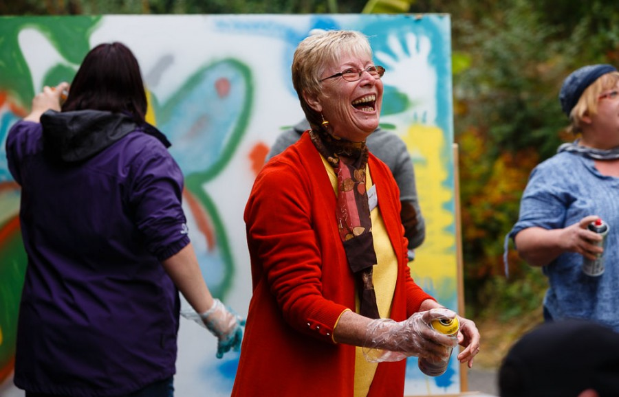 A woman laughing with a can of spray paint in her hand.
