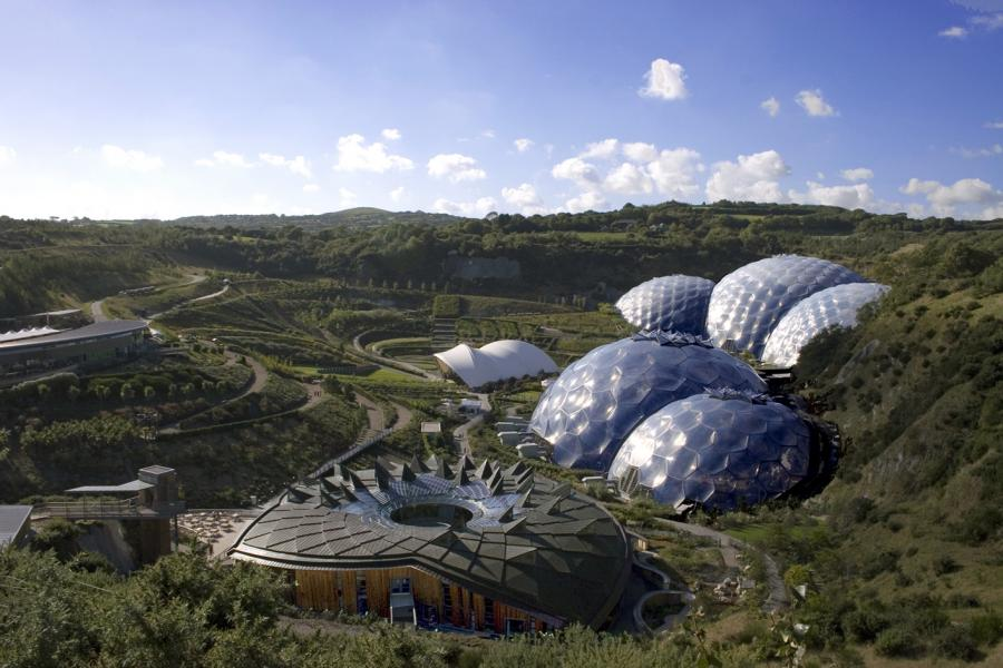A picture of the Eden Project showing two domed greenhouses, the educational centre and the outside gardens