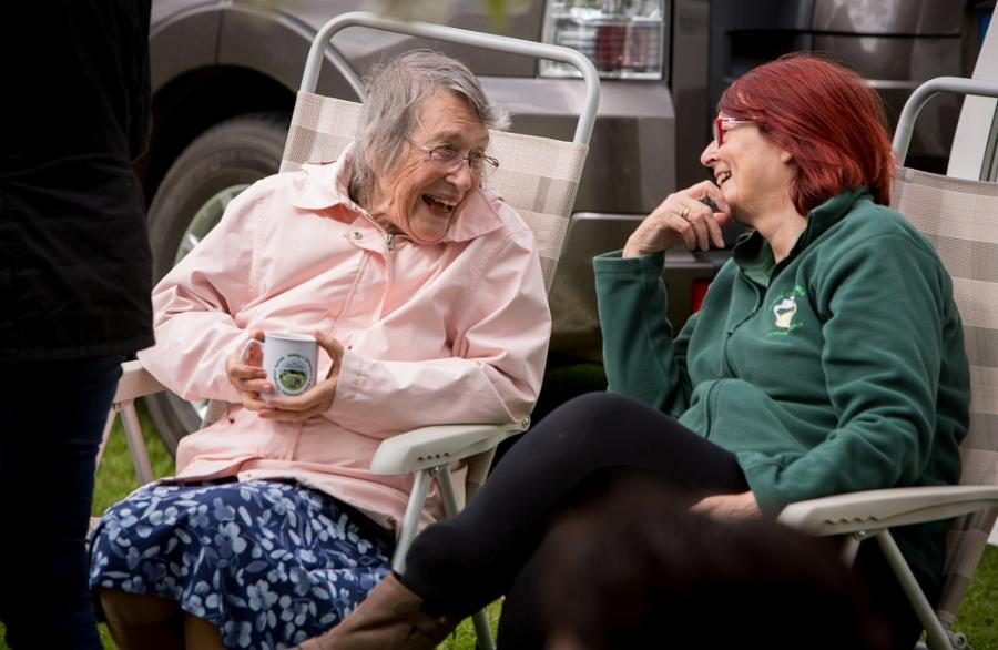 An elderly woman sits smiling at another woman.