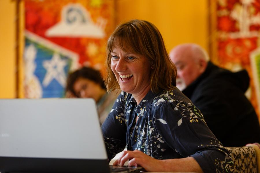 A woman sat smiling in front of a laptop computer.