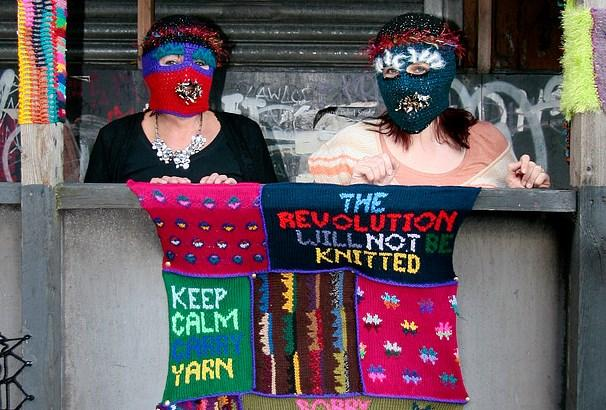 Two women wearing knitted multicoloured balaclavas lean over a wall and hold a knitted slogan.