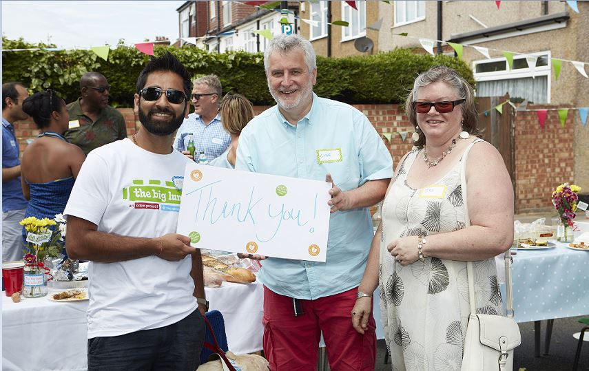 Amit Patel at a Big Lunch holding a Thank You sign with two neighbours