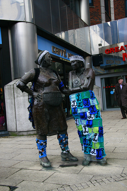 A statue of two women on which someone has placed kitted garments.
