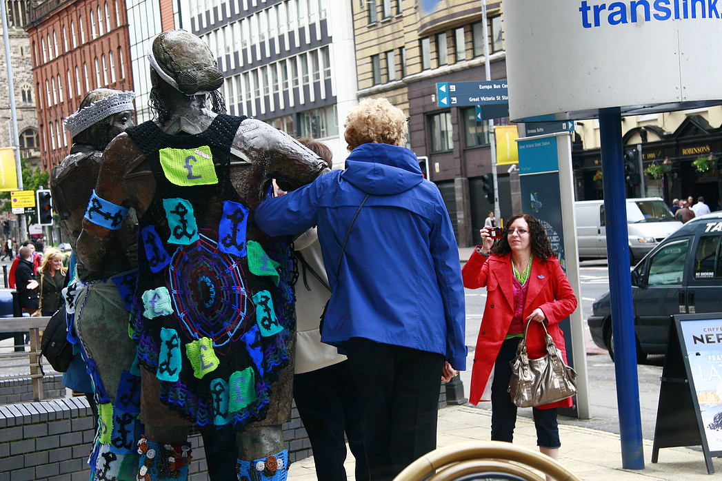 A statue of two women on which someone has placed knitted garments.