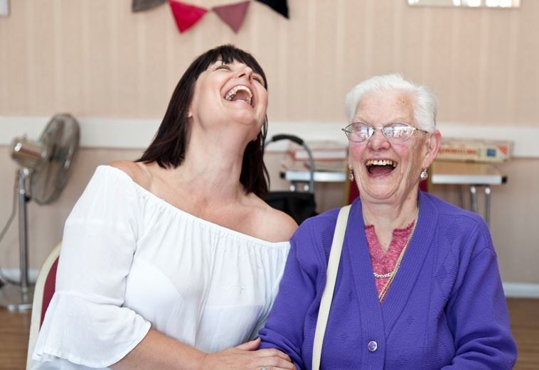 Photo of ladies of different ages laughing together